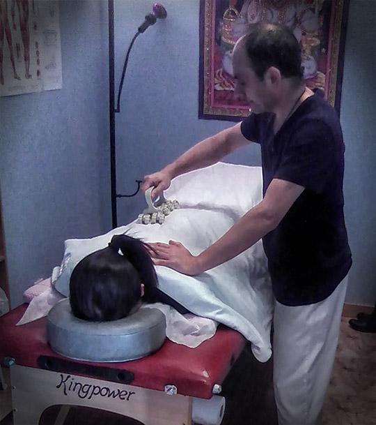 Carlos aplicando el infrarrojos lejanos a un paciente